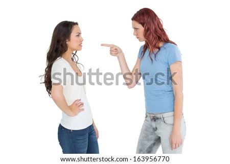 Side view of angry young female friends having an argument over white background - stock photo