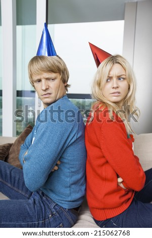 Side view of annoyed couple in Christmas sweaters and party hats sitting back to back at home - stock photo