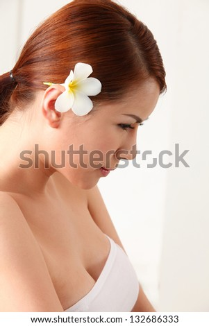 side view of asian woman with frangipani in her ear