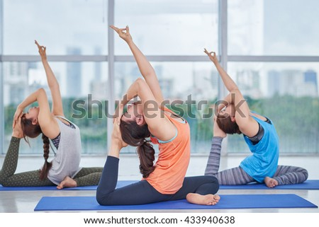 Side view of Asian women practicing pigeon asana in class - stock photo
