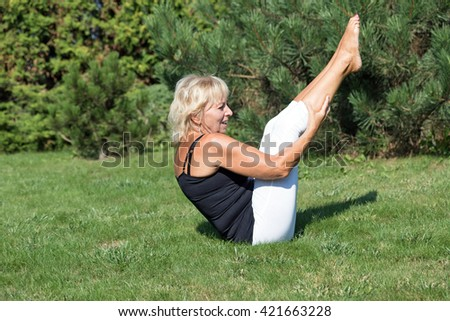 Side view of attractive blond senior woman is stretching exercising outdoors. The woman is sitting on the lawn, her hands are holding the legs, her body is forming the letter V. - stock photo