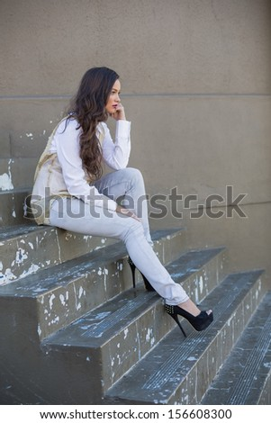 Side view of attractive brunette sitting on stairs - stock photo