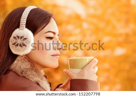 Side view of attractive female have coffee in autumnal park, gorgeous arabic girl wearing stylish head clothes on orange foliage background, autumn concept - stock photo