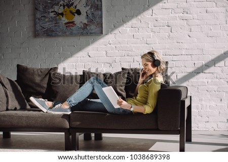 side view of attractive girl watching movie on tablet at home