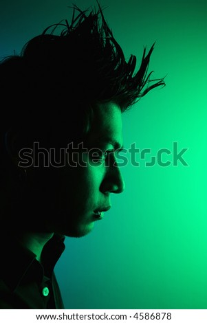 Side view of attractive young Asian man with spiked hair. - stock photo