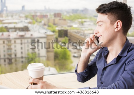 Side view of attractive young man having mobile phone conversation and drinking coffee inside on blurry city background