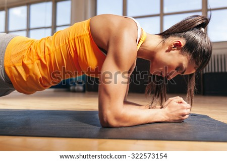 Side view of attractive young woman doing core exercise on fitness mat in the gym. Female doing press-ups in health club. - stock photo