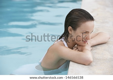 Side view of attractive young woman resting on the edge of swimming pool