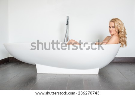 Side View of Beautiful Blond Woman Looking at Camera and Relaxing in Modern Bathtub