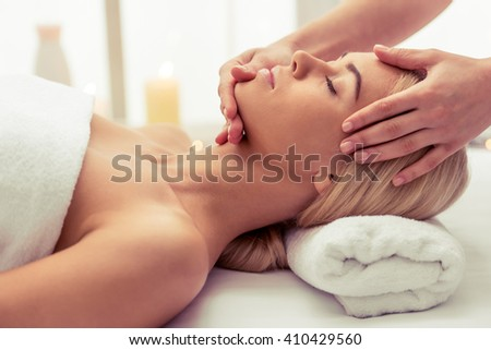 Side view of beautiful blonde girl lying with closed eyes at spa while a massage therapist is massaging her head - stock photo
