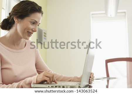 Side view of beautiful businesswoman using laptop in office - stock photo
