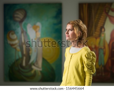 side view of beautiful caucasian woman contemplating artworks in an art museum  - stock photo