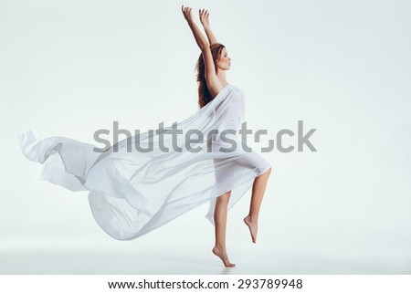 Side view of beautiful naked woman with flying white cloth on her body standing on one leg and hands raised. Sensual model posing over white background with copyspace. - stock photo