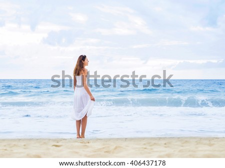 Side view of beautiful woman in white dress enjoying the idyllic scene on the beach.