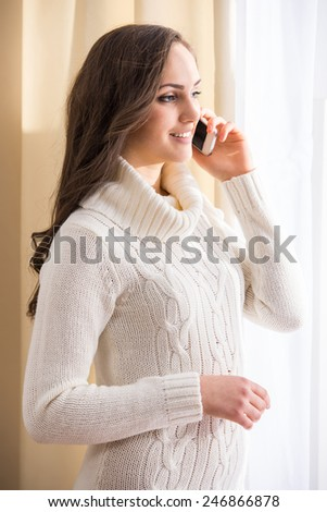 Side view of beautiful woman is talking on phone. - stock photo