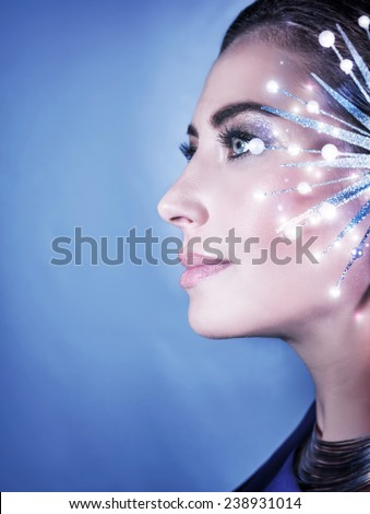 Side view of beautiful woman portrait on blue background, gorgeous female with shiny snowflake accessories, Fashion Christmas look - stock photo