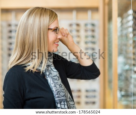 Side view of beautiful woman trying on glasses in optician store - stock photo