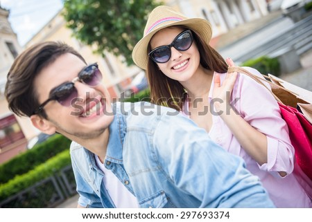 Side view of beautiful young couple riding scooter, happy woman holding bags. Shopping together.