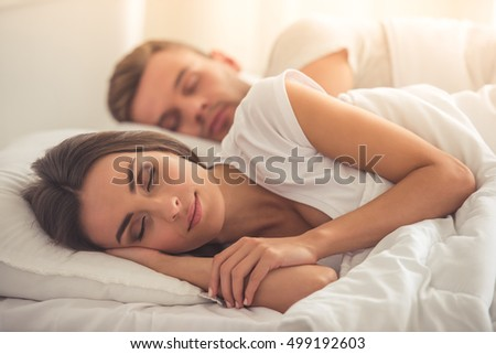 Side view of beautiful young couple sleeping in bed at home