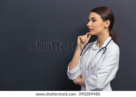 Side view of beautiful young doctor in white medical gown keeping hand on chin and thinking, against blackboard - stock photo