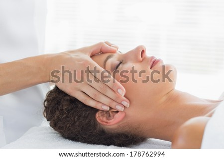 Side view of beautiful young woman receiving head massage in health spa - stock photo