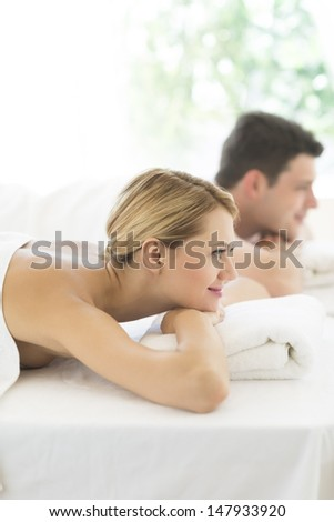 Side view of beautiful young woman resting on massage table with man in background at health spa