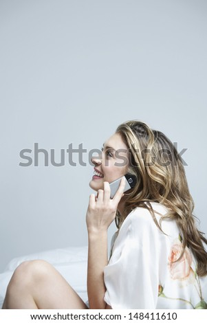 Side view of beautiful young woman using mobile phone in bed - stock photo