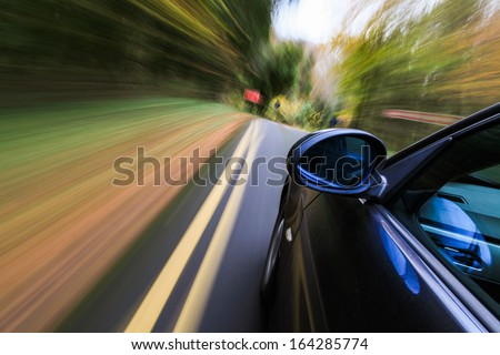 Side view of black sedan with heavy blurred motion. - stock photo