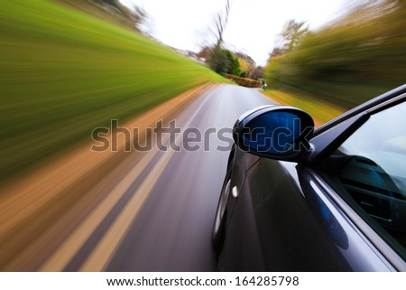 Side view of black sedan with heavy blurred motion.