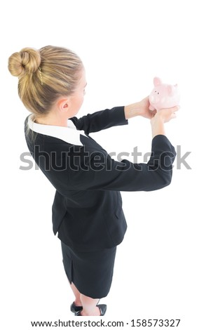 Side view of blonde businesswoman holding a piggy bank looking at it