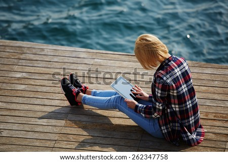 Side view of blonde hair woman using digital tablet while sitting on a wooden pier next to the sea, female tourist busy use tablet while sitting outdoors at sunny day, girl browsing outside - stock photo