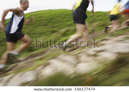 Side view of blurred group of people running on track - stock photo