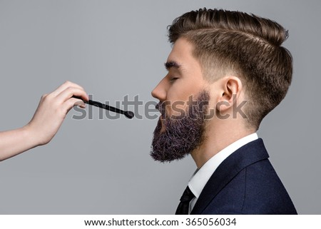 Side view of brunette man with violet beard and eyebrows, wearing in dark blue suit and tie. Woman's hand with make-up brush near his face, on white background, in studio, close up - stock photo
