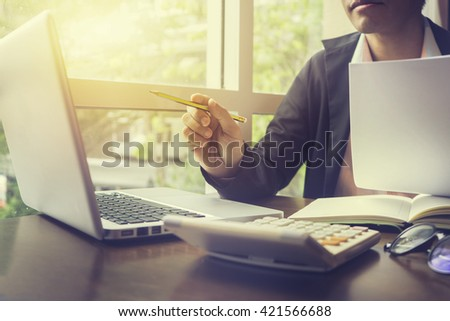 side view of Business man working at office with laptop and documents on his desk at his office while looking serious consultant ,lawyer concept,morning light,vintage color,selective focus - stock photo