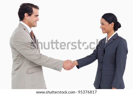 Side view of business partners shaking hands against a white background