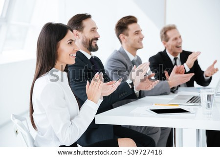 Side view of Business people are applauded and sitting by the table in office