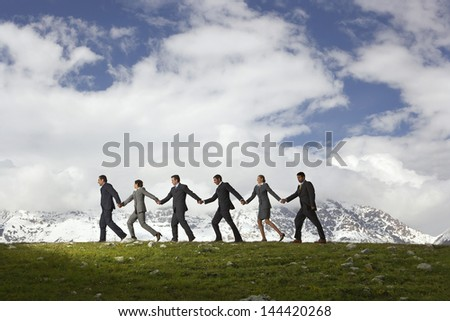 Side view of business people holding hands and walking through mountains - stock photo