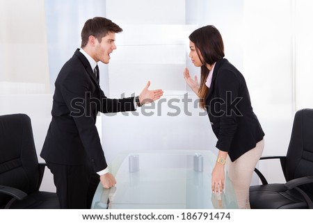 Side view of business people quarreling at desk in office - stock photo