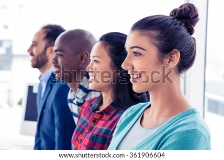 Side view of business people standing in row at creative office