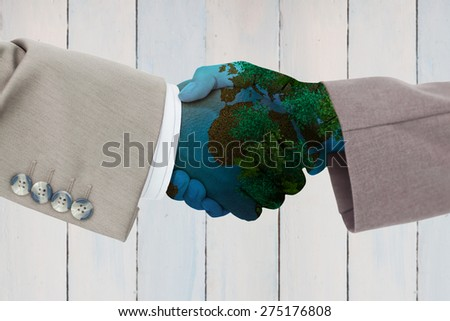 Side view of business peoples hands shaking against wooden planks - stock photo