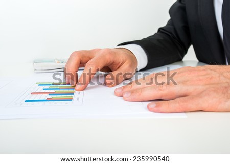 Side view of businessman analysing a set of bar graphs as he sits at his white desk pointing to one column chart, in a business analysis and strategy concept. - stock photo