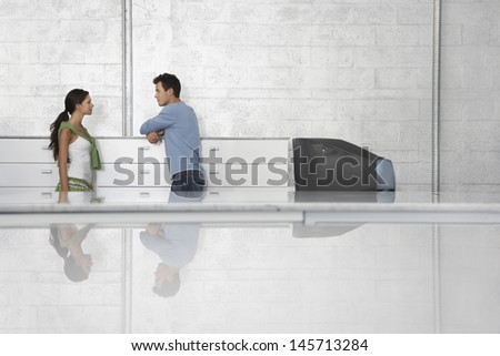 Side view of businessman and businesswoman leaning on cabinet in office - stock photo