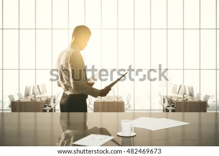 Side view of businessman examining contract on modern office with workplace, coffee cup, other items and windows with sunlight. 3D Rendering