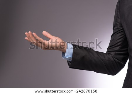 Side view of businessman hand gesture isolated on gray background. Successful business man concept. empty palm - stock photo