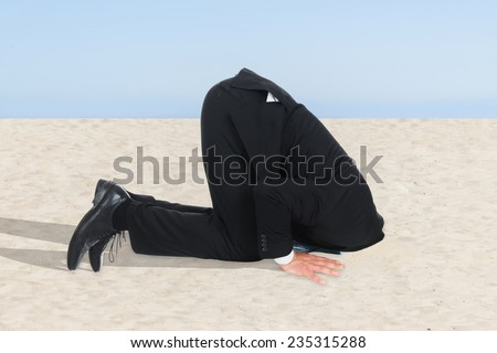 Side view of businessman hiding his head in sand - stock photo