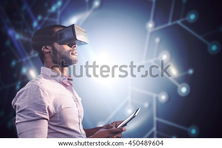 Side view of businessman holding virtual glasses and tablet computer against black background with glowing network - stock photo