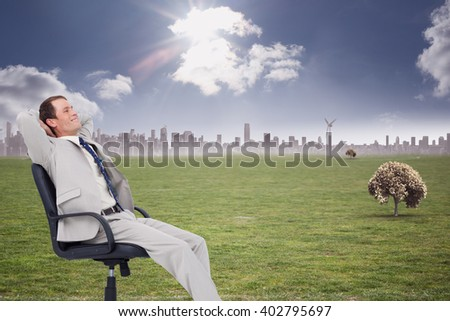 Side view of businessman leaning back in his chair against cityscape on the horizon