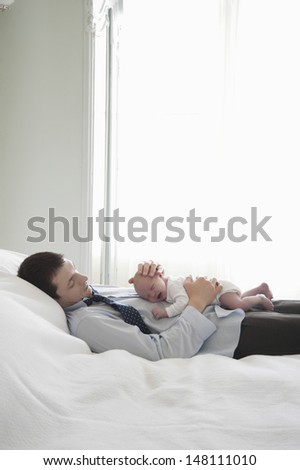Side view of businessman lies with two week newborn on bed - stock photo