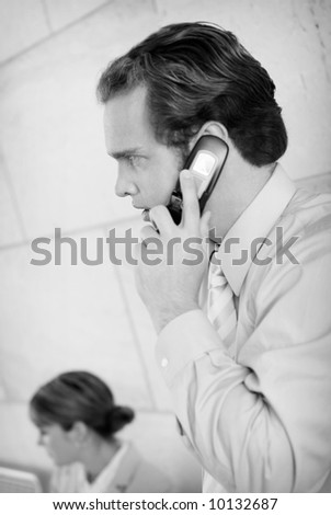 side view of businessman standing and businesswoman sitting