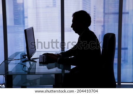Side view of businessman using computer in office